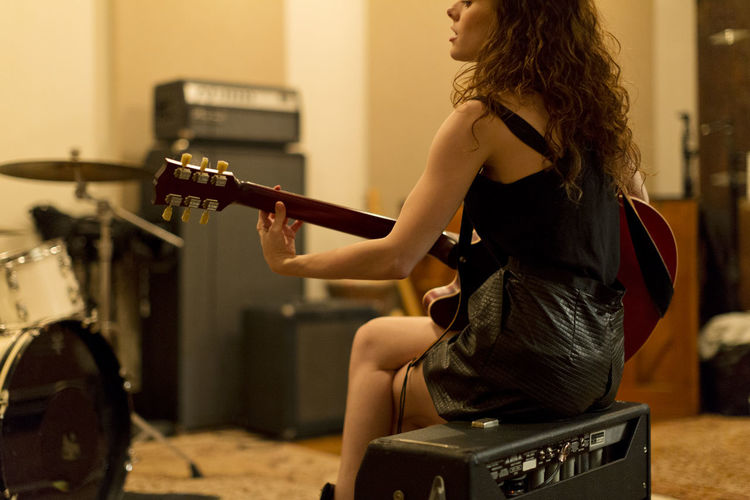 Woman sitting on guitar