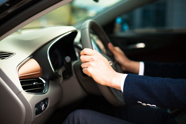Cropped image of businessman driving car