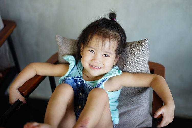Portrait of girl smiling while sitting on chair at home
