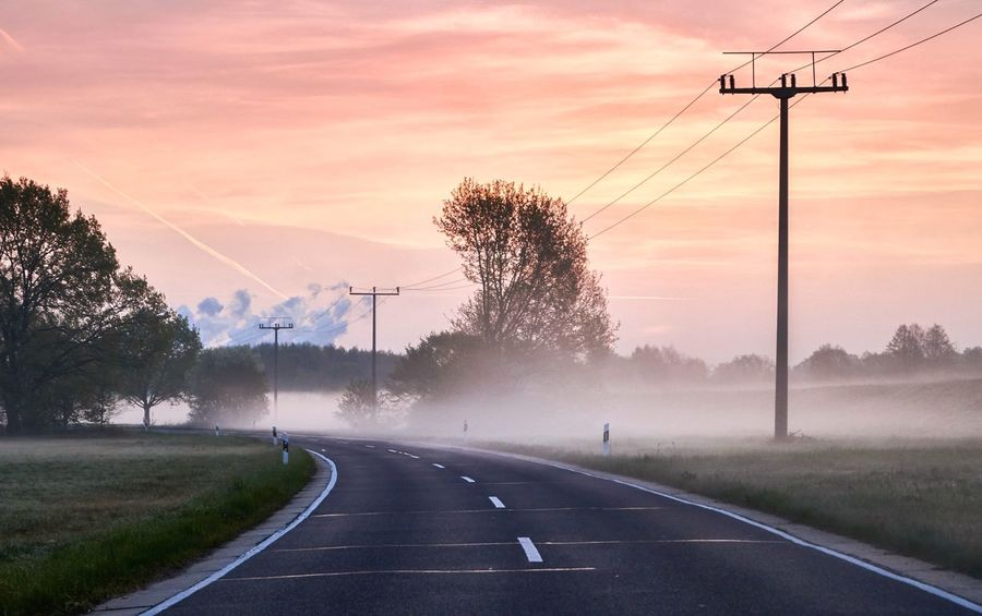 Road while sunrise and fog Fog Wanderlust Outdoors Road Transportation Sky Direction The Way Forward Sign Cloud - Sky Connection Tree Nature Plant Technology Symbol Electricity  Electricity Pylon No People Diminishing Perspective Sunset Power Line  Cable Summer Exploratorium