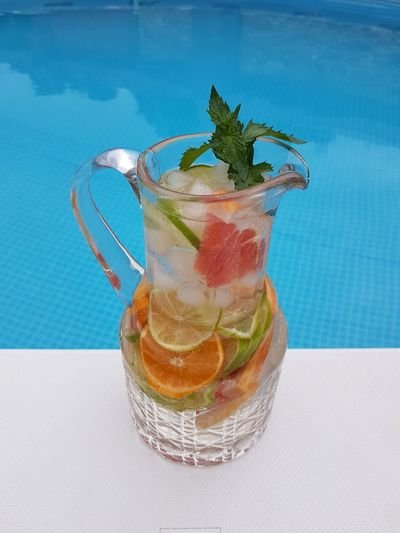 Cocktail on table by swimming pool