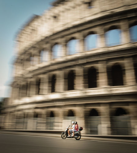 Blurred Motion Of People Riding Motor Scooter On Road Against Coliseum