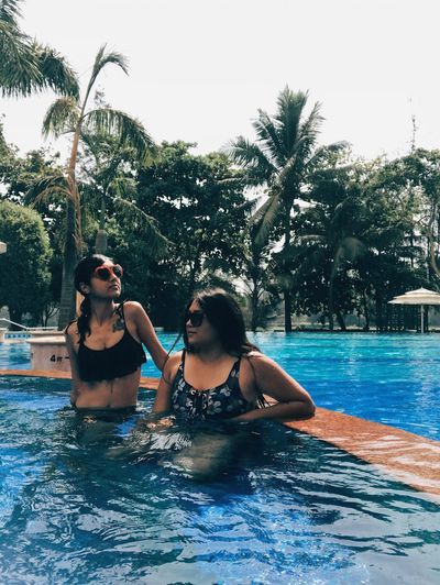 Swimming Pool Water Vacations Leisure Activity Bikini Two People Palm Tree Tree Togetherness Enjoyment Real People Young Adult Lifestyles Tourist Resort Young Women Day Happiness Outdoors Smiling Friendship Connected By Travel