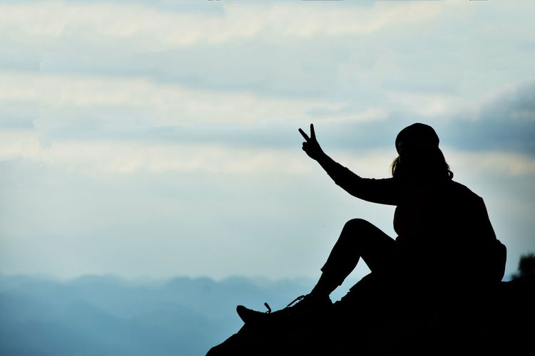 Woman Gesturing Peace Sign While Sitting On Cliff Against Sky