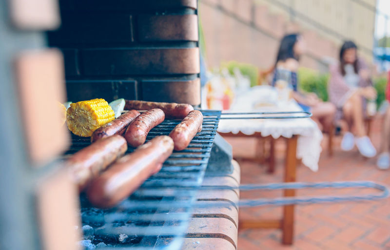 Close-up of sausages and corn on barbecue grill with friends sitting in background