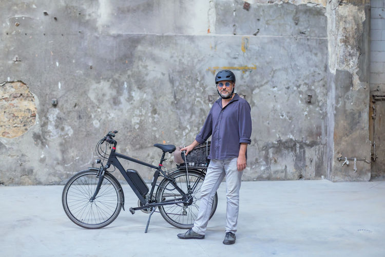 Portrait of man with bicycle standing in city
