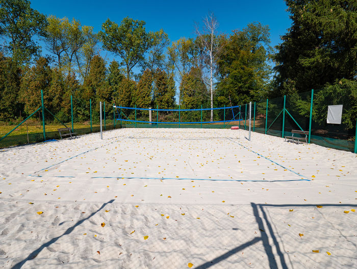 Closed beach volleyball court in fall season. autumn weather and fallen leaves on white sand.