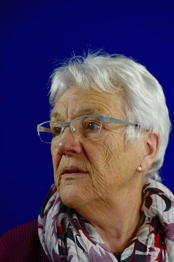 Close-up of thoughtful senior woman wearing eyeglasses against blue background