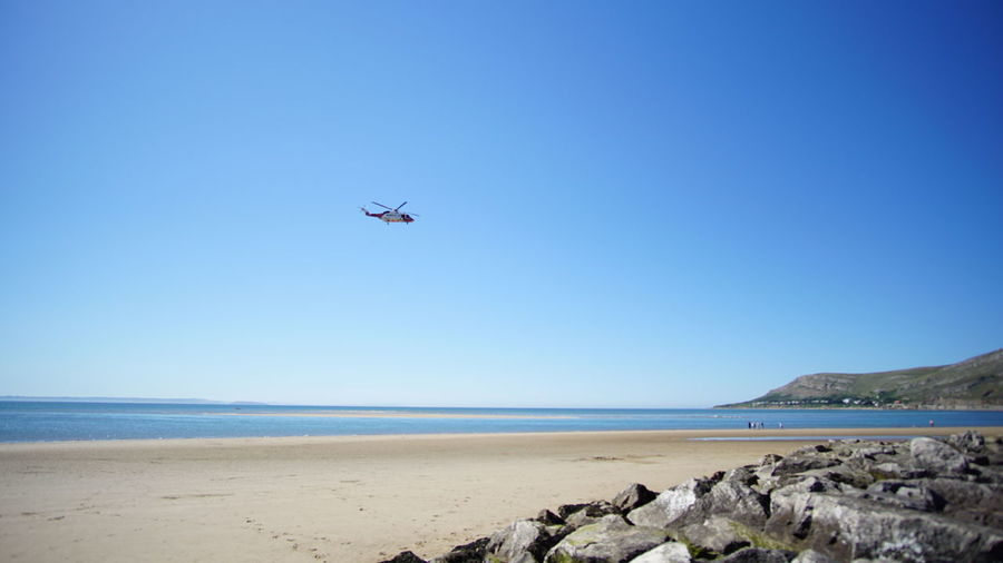 Helicopter Wales Air Vehicle Airplane Beach Beauty In Nature Blue Break Clear Sky Day Flying Horizon Over Water Llandudno Nature No People Outdoors Rocks Sand Sea Sky Sun Transportation Uk Water