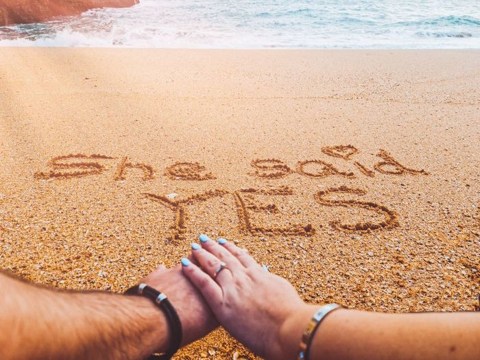 Midsection of text on sand at beach - marriage proposal