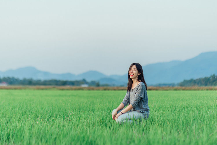 Full length of smiling woman on field