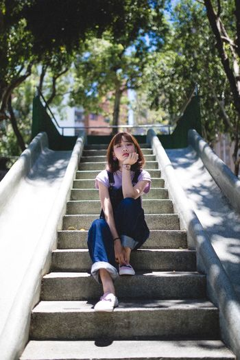 Full Length Staircase One Person Sitting Lifestyles Leisure Activity Real People Casual Clothing Architecture Steps And Staircases Plant Young Women Front View Young Adult Women Tree Day Nature Wireless Technology Hairstyle