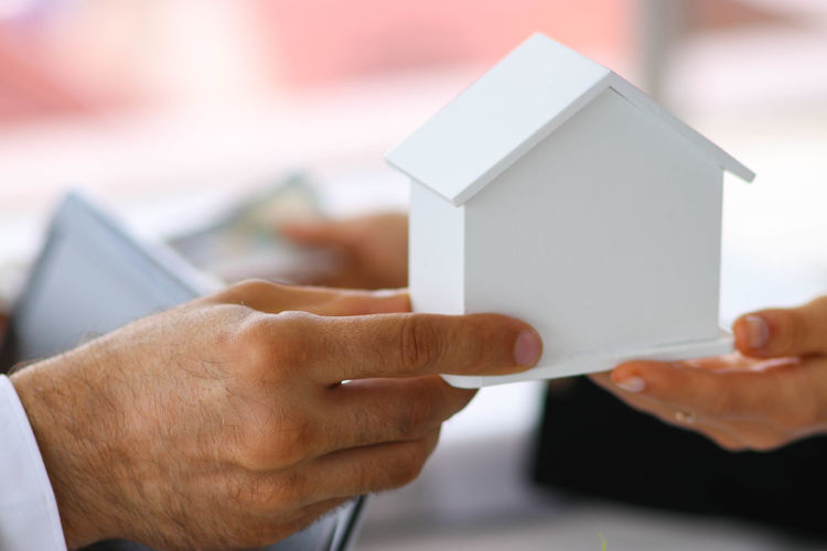 Home buying, concept, real estate investment and speculation. Adult Business Hand Holding Human Body Part Human Hand Indoors  Paper
