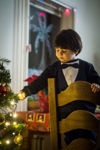 Boy touching illuminated christmas tree while standing on chair at home
