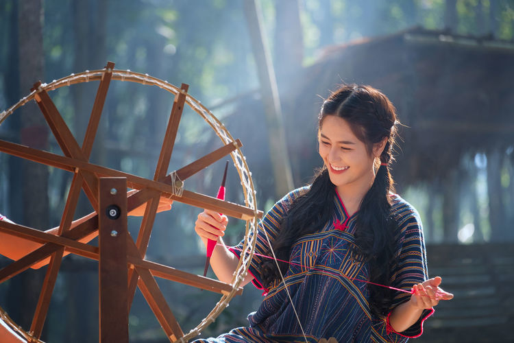 Young woman weaving thread on wheel against house