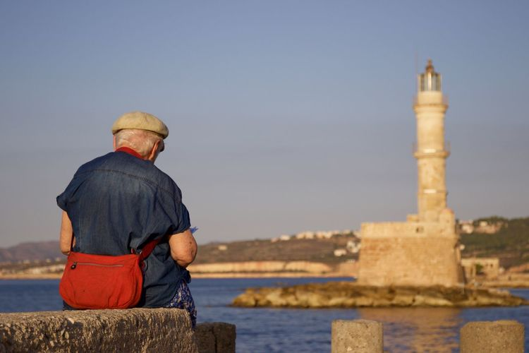 Rear view of senior man sitting on retaining wall with chania lighthouse in background