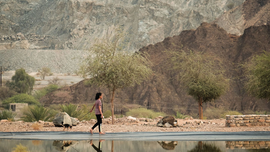 A young female teenager walking with a small dog in the mountains beside a clear mirror lake in Hatta, United Arab Emirates One Person Water Full Length Day Nature Mountain Outdoors Adult Mammal One Animal Rock Rock - Object Domestic Animals Tree Domestic Solid Pets Reflection Hiking Camping Adventure Walking Dog Exercise Early Morning