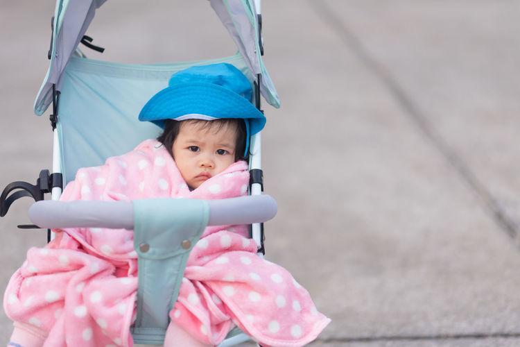 Portrait of cute girl sitting in baby stroller