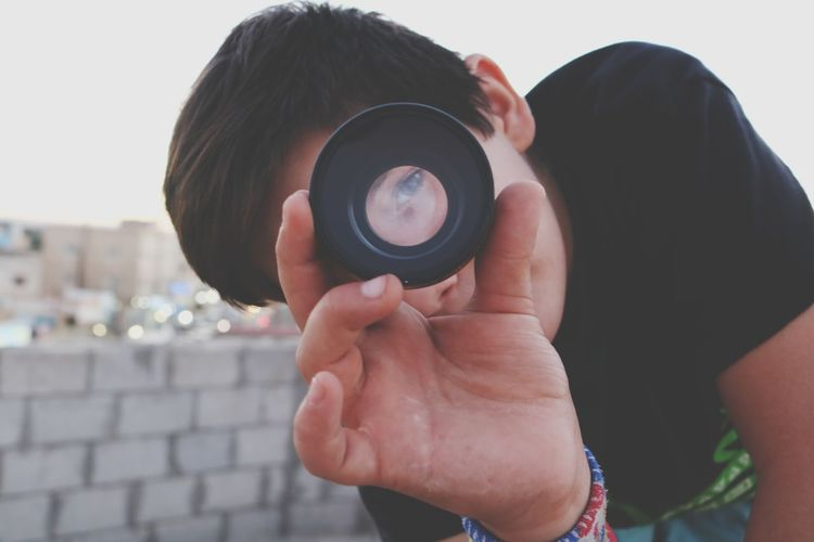Portrait of boy looking through camera lens