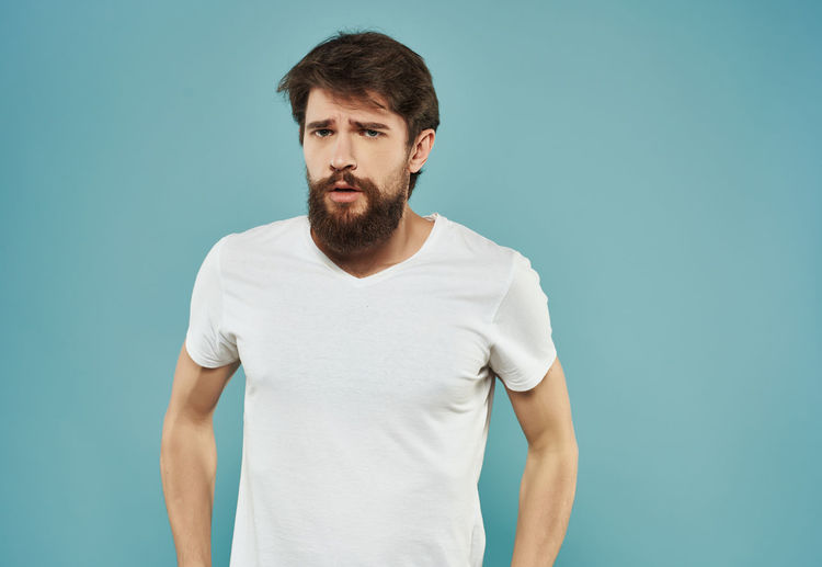 Portrait of young man standing against blue background