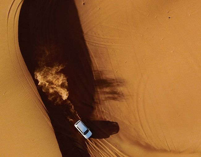 Directly above shot of off-road vehicle moving in desert