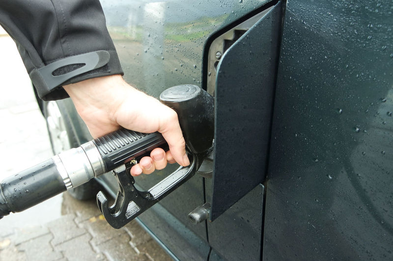 Cropped hand filling fuel in car