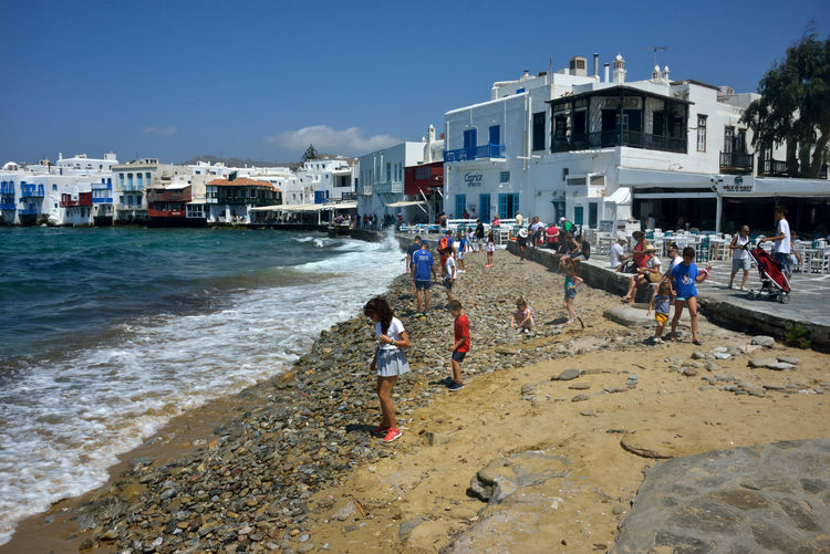 view of Little Venice in Mykonos with people on the beach playng and relaxing Water Architecture Building Exterior Built Structure Sea Sky Beach Group Of People Nature Land Day Real People Child Women Building Boys Men People Clear Sky Outdoors Little Venice Mykonos Mykonos,Greece Relaxing People Children Playing On A Beach Tourist Highlights Seafront Cityscape Greek Architecture Youth Travel Destinations