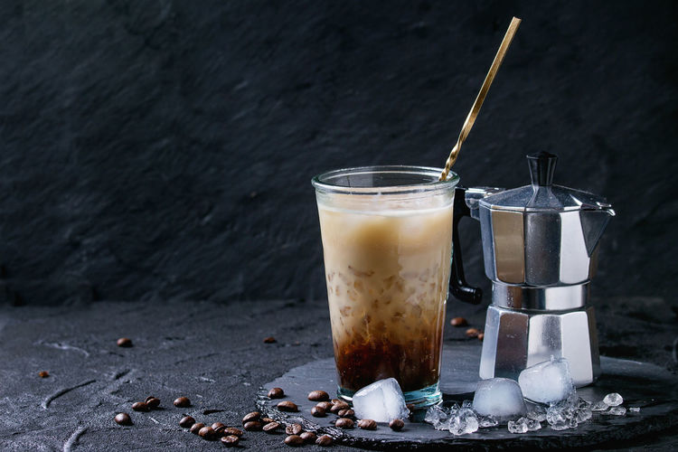 Glass of ice coffee with cream and milk, served with coffee beans, ice cubes and coffee pot on slate stone board over black textured background. Food And Drink Drink Refreshment Glass Food Freshness Coffee Coffee - Drink Iced Coffee Frappe Cold Drink Glass - Material Coffee Beans Cocktail Dark Black Drinking Glass Dairy Product Table Cold Temperature