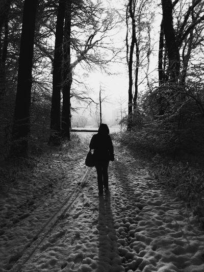 Rear View Of Woman In Hood Standing On Snowy Field