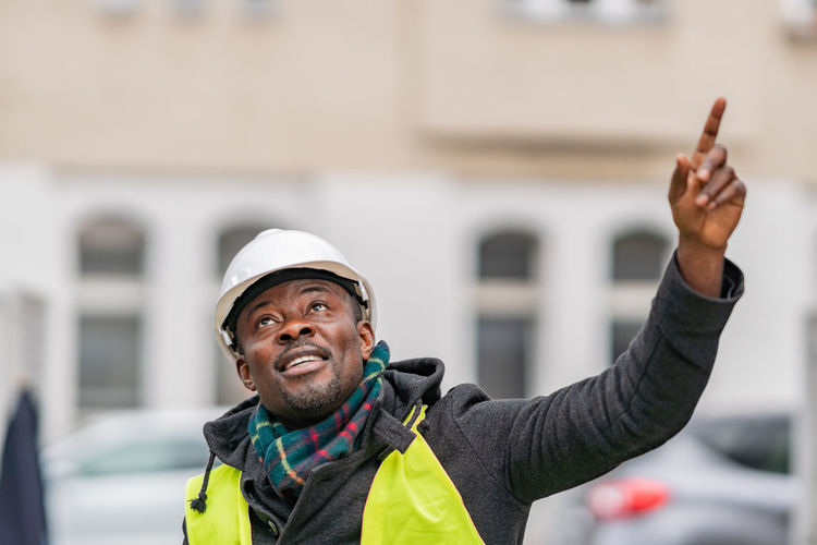 Thoughtful male engineer pointing while standing against building in city