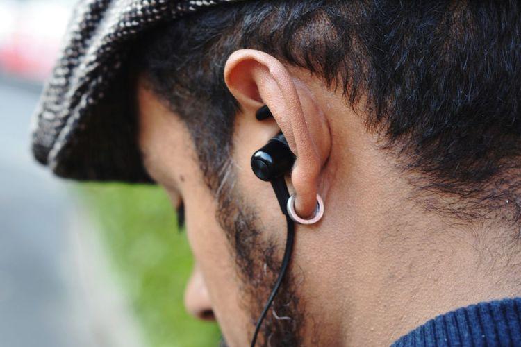 Close-up of man listening music through headphones