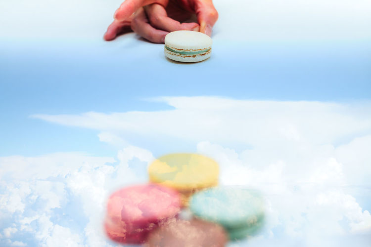 Digital composite image of person striking macaroon and cloudy sky