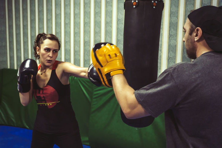 Female Boxer Training With Male Fitness Instructor In Gym