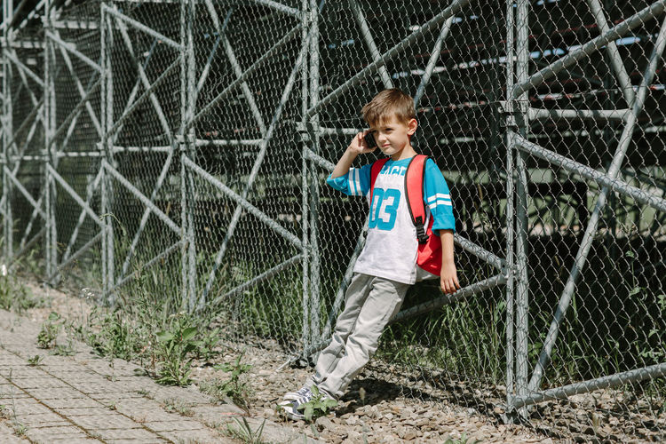 Full length of boy talking on mobile phone while leaning against chainlink fence