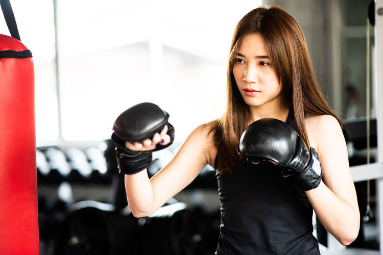 Young woman punching bag while standing in gym