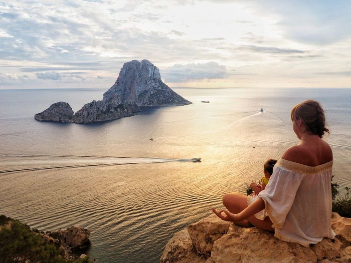 Mother meditating while sitting with daughter on cliff against sea