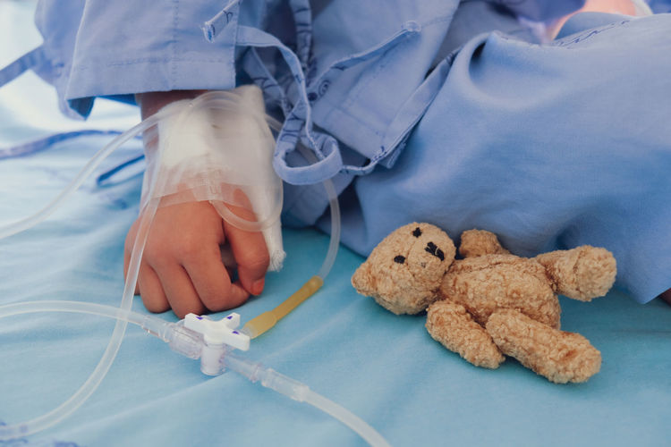 Cropped image of child sitting with teddy bear on bed in hospital
