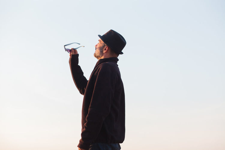 Side view of person wearing hat standing against clear sky