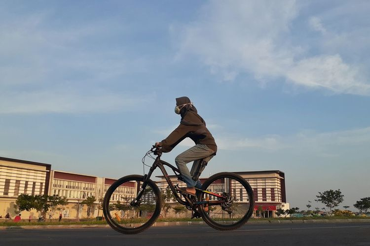Side view of man cycling on bicycle against sky