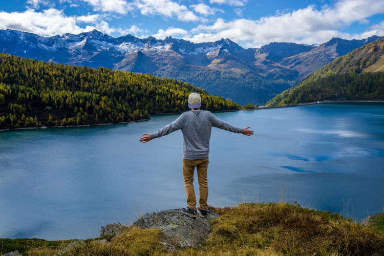 men standing infront of a mountain like during autumn Arms Outstretched Arms Raised Beauty In Nature Casual Clothing Cloud - Sky Human Arm Idyllic Lake Leisure Activity Limb Looking At View Mountain Nature Non-urban Scene One Person Outdoors Real People Rear View Scenics - Nature Sky Standing Tranquil Scene Tranquility Water