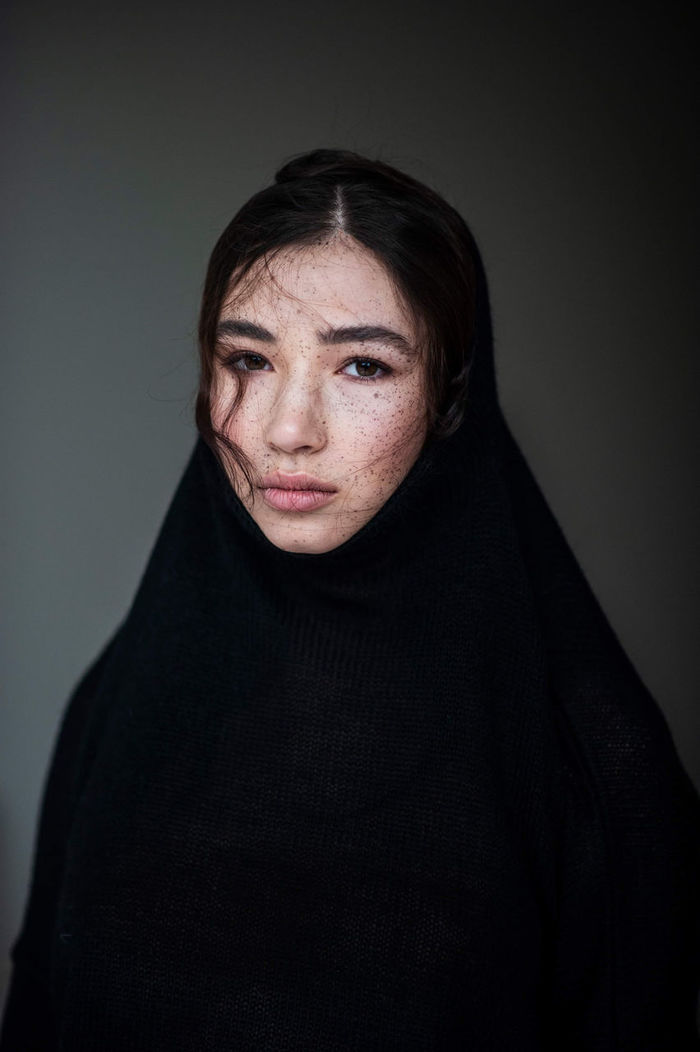Portrait of woman in black scarf against gray background