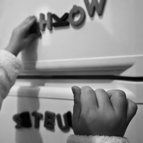 Cropped image of child hand playing with letter magnet on refrigerator