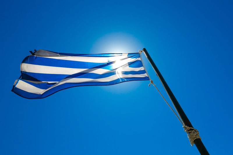 Low angle view of greek flag against clear blue sky