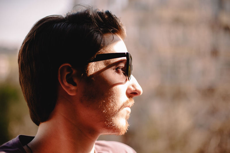 Portrait of young man looking away outdoors
