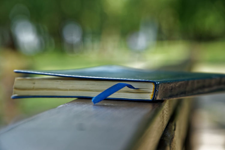 Close-up of book on wooden railing