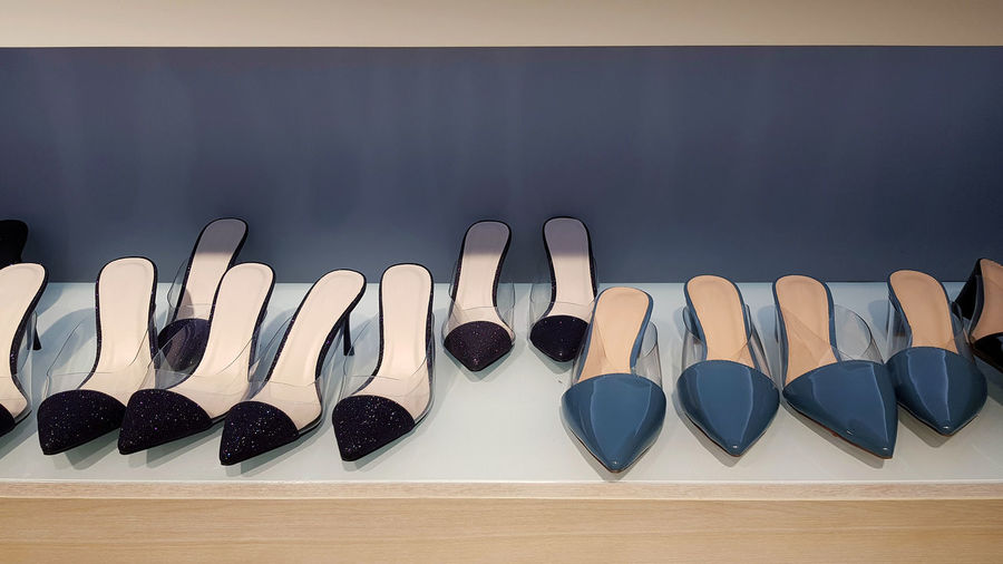 Close-up of shoes arranged on table against wall