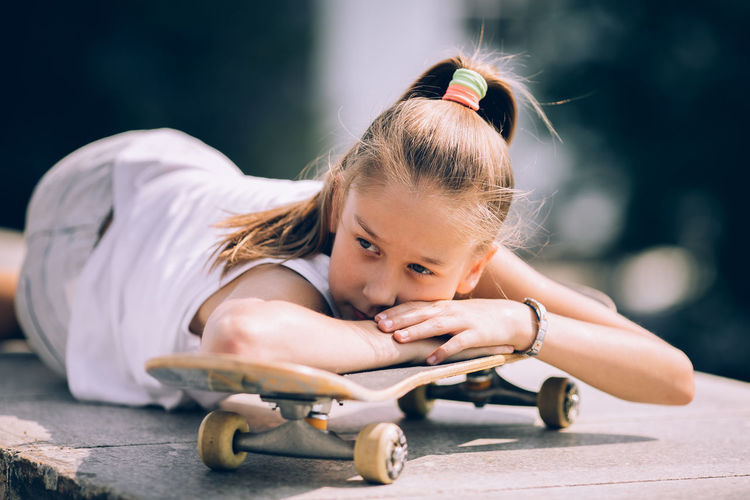 Portrait of cute girl sitting outdoors on skateboard