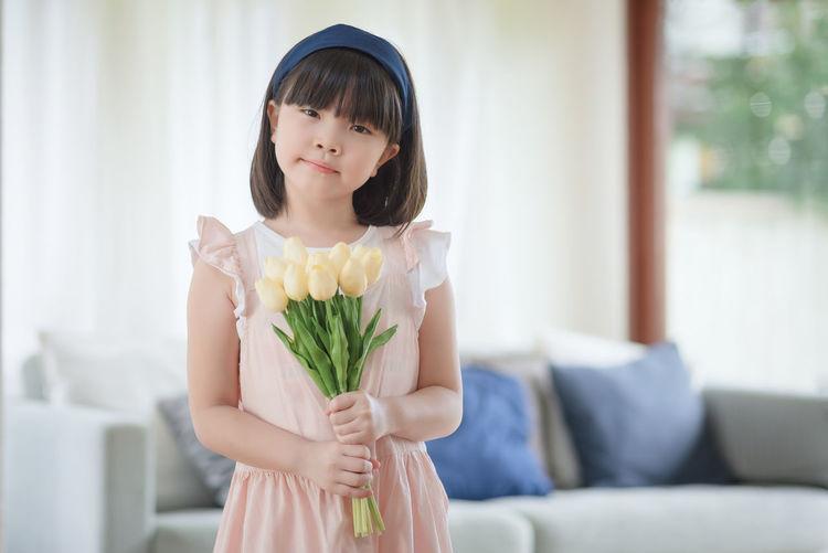 Girl holding flower at home