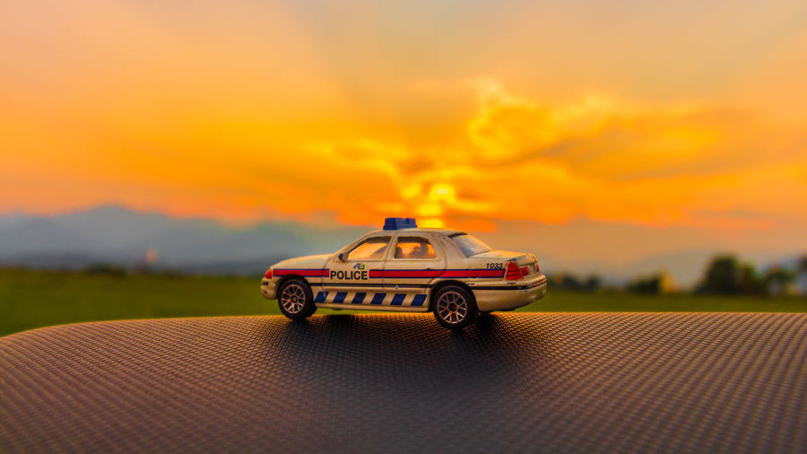 Toy car on road against sky during sunset