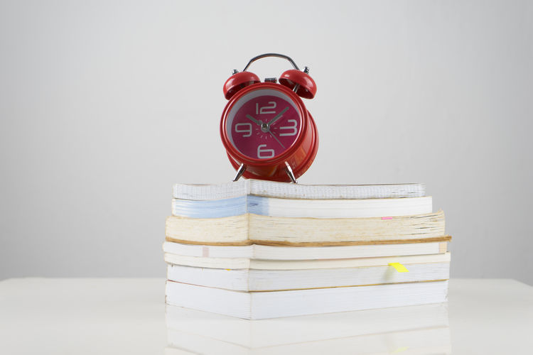 Close-up of alarm clock on stacked book against gray background